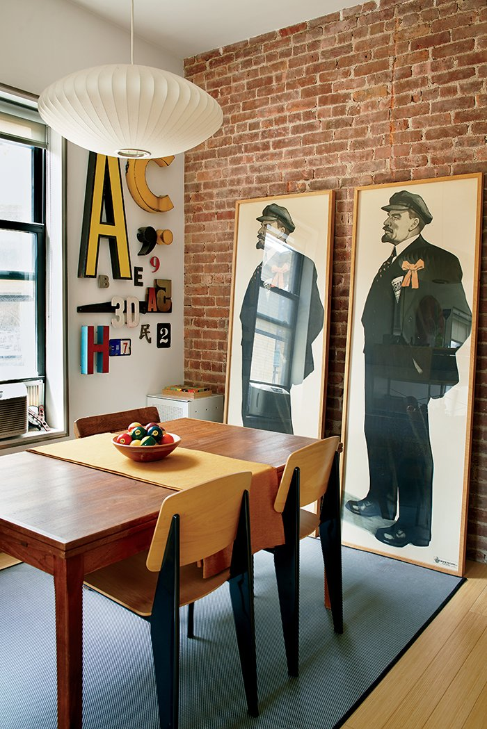 """The Vladimir Lenin prints were a gift from Drew's father, also a graphic designer, and reflect their shared love of """"graphically powerful types of printed ephemera,"""" Drew says. Standard chairs by Jean Prouvé for Vitra are tucked under the dining table. Tagged: Dining Room, Chair, Table, Pendant Lighting, Rug Floor, and Light Hardwood Floor.  Photo 2 of 12 in Bright Renovation of a Tiny Manhattan Apartment"""