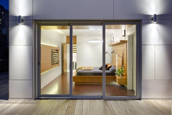 The emphasis on linearity and natural materials continues into the master bedroom, where the flooring is a brown leather plank floor from Torlys. The bedside lights are from Dark Tools.