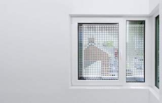"""Inside, perforated window screens reference the light fixture in the courtyard, """"offering an abstract, fragmented glimpse of the tulips inside,"""" explains Harland."""