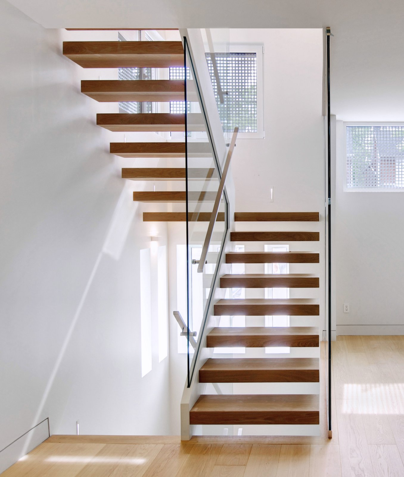 Another peek at the perforated interior windows, which are made from cropped sections of the steel wall in the courtyard.  190+ Best Modern Staircase Ideas by Dwell from From a Flower Bulb Factory to an Entertainment Hub