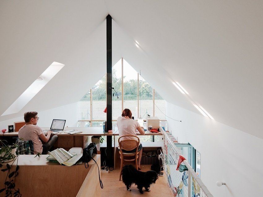 Balanced above the central core, the office offers an ideal perch for work with a west-facing skylight that provides natural illumination for the shared desk space. Tagged: Office, Chair, Medium Hardwood Floor, and Desk.  Photo 7 of 8 in Small Country Home with Dramatic See-Through Wall