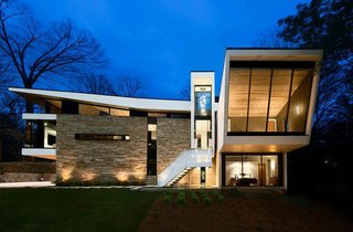 "A Wing-Roofed Home in Georgia Perches Among the Trees - Photo 1 of 7 - ""So many houses seem like they're completely still and heavy,"" says Dencity architect Staffan Svenson. Inspired by his client's role in the airline industry, Svenson relished the chance to create a home that evokes motion and lightness."