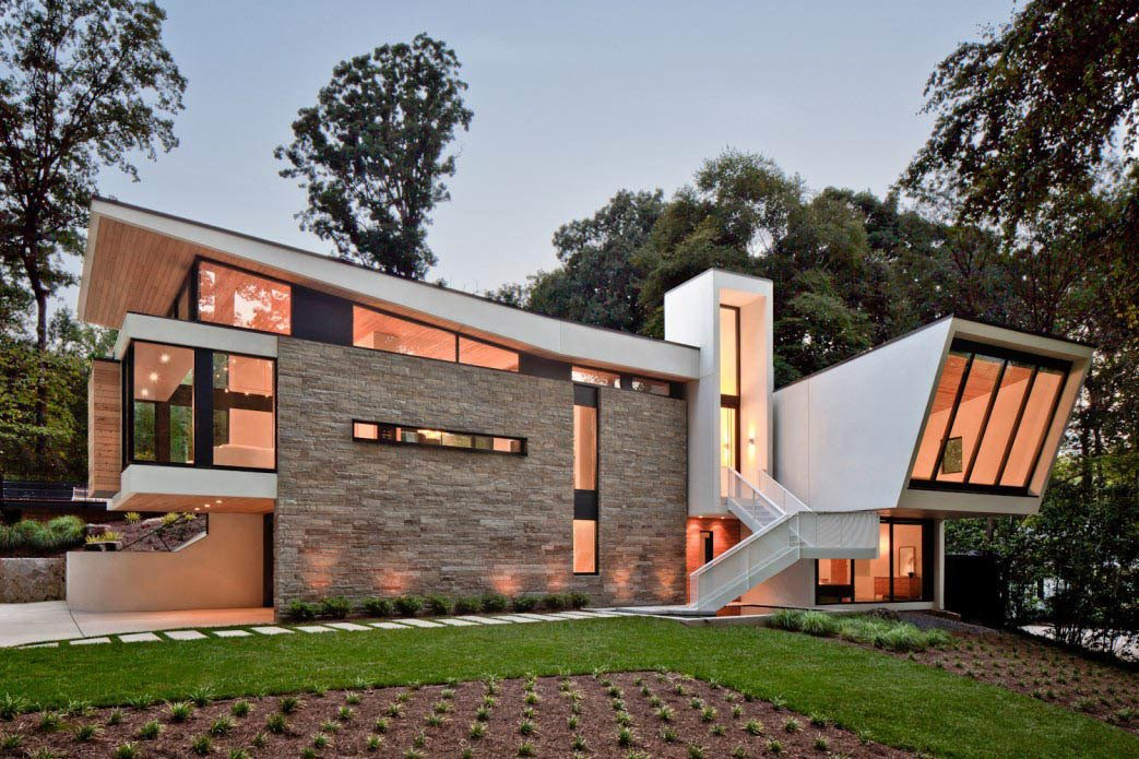 "Svenson calls the floating aluminum stairway ""a major sculptural element."" He adds, ""We really wanted to celebrate the entry,"" which is elevated because the site is ten feet higher in the rear. The earthy stucco and local stone cladding keep the home rooted to its landscape.  Photo 2 of 7 in A Wing-Roofed Home in Georgia Perches Among the Trees"
