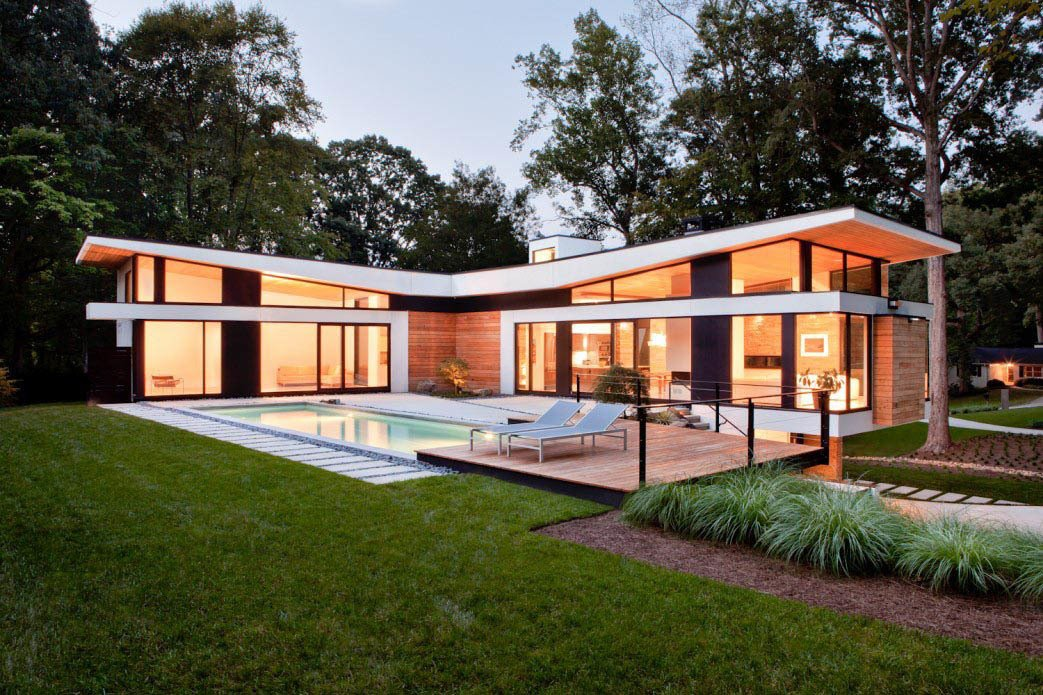 """The home's T-shaped layout forms a courtyard accessible by its two """"social wings,"""" fitted with massive Kawneer sliding doors made for auto showrooms.  Photo 3 of 7 in A Wing-Roofed Home in Georgia Perches Among the Trees"""