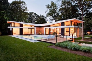 "A Wing-Roofed Home in Georgia Perches Among the Trees - Photo 3 of 7 - The home's T-shaped layout forms a courtyard accessible by its two ""social wings,"" fitted with massive Kawneer sliding doors made for auto showrooms."