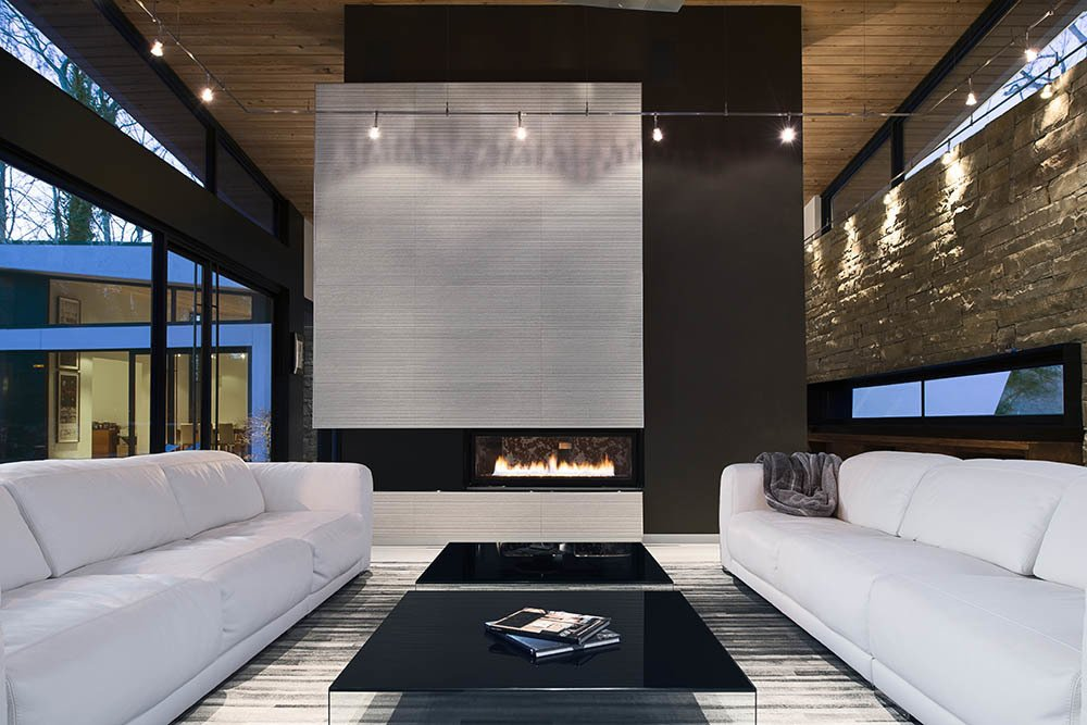 The clients asked for interior products in thirteen shades of white, including the twin Malibu sofas by American Leather. Interior designer Burns Century added deeply hued textures such as the charcoal suede on the fireplace column to keep the room feeling natural, not icy. The black Pool coffee tables are from Design Within Reach. A Wing-Roofed Home in Georgia Perches Among the Trees - Photo 4 of 7