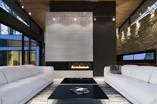 A Wing-Roofed Home in Georgia Perches Among the Trees - Photo 4 of 7 - The clients asked for interior products in thirteen shades of white, including the twin Malibu sofas by American Leather. Interior designer Burns Century added deeply hued textures such as the charcoal suede on the fireplace column to keep the room feeling natural, not icy. The black Pool coffee tables are from Design Within Reach.