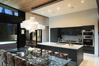 A Wing-Roofed Home in Georgia Perches Among the Trees - Photo 5 of 7 - Candy Sarvis loves feeling connected with dinner guests while she cooks. The African teak kitchen cabinetry is by Pedini, with Miele appliances. A Big Bang pendant by Foscarini illuminates the Montecarlo table by Cattelan Italia.