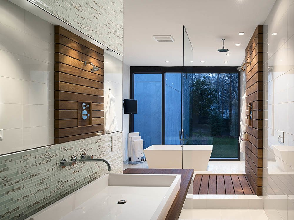 In the master bath, a custom raised Silestone sink is surrounded by a teak countertop and Porcelanosa glass tiles. Teak slats anchor the glass-enclosed shower. Tagged: Bath Room, Wood Counter, Vessel Sink, Glass Tile Wall, Freestanding Tub, and Open Shower.  Photo 14 of 14 in Inspired Indoor Teak Looks from A Wing-Roofed Home in Georgia Perches Among the Trees