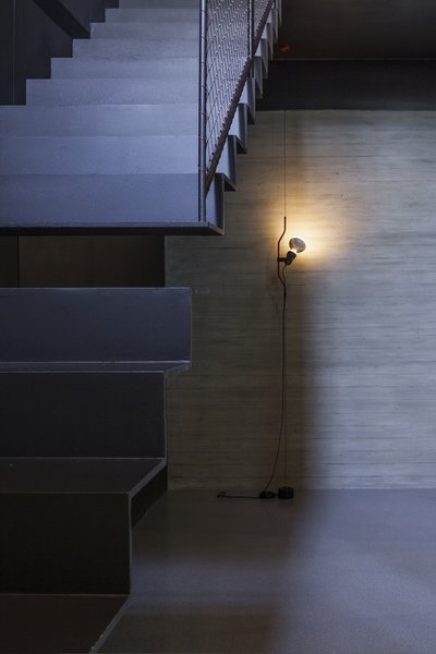 Pitsou Kedem's unique twist in the new basement is a two-part metal staircase with a gap in the middle. A slim Parentesi Floor Lamp illuminates the space. Photo 4 of Minimal Reboot modern home