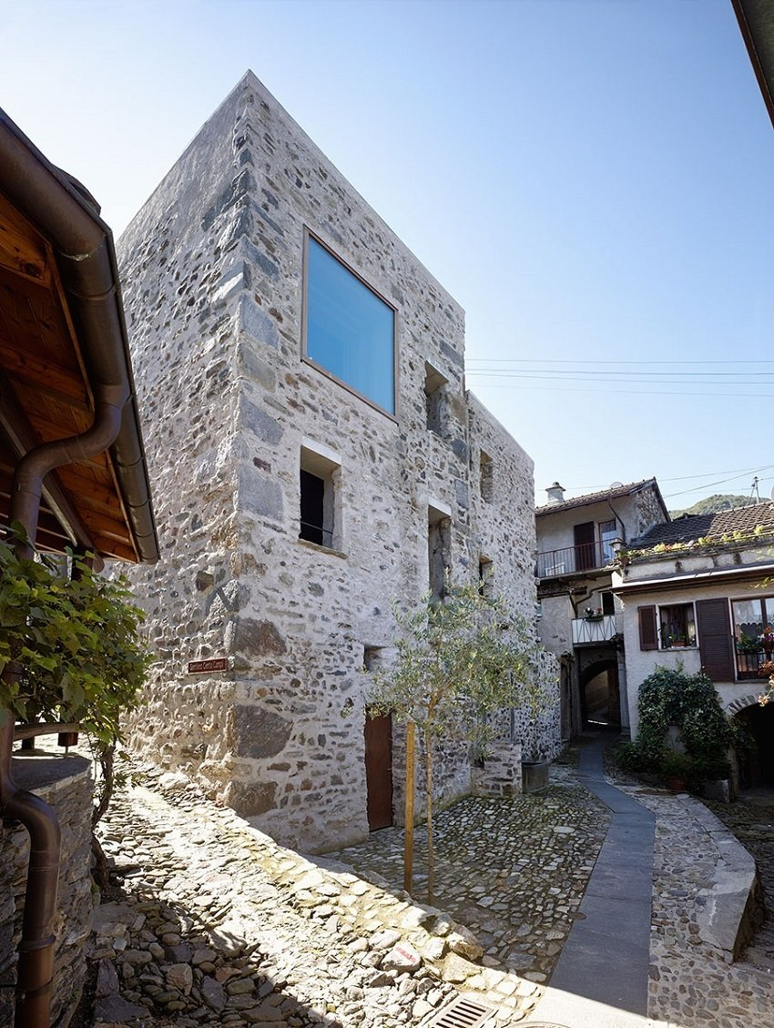 "The end goal, a vacation home with a view of the nearby lake, led Jérôme de Meuron to cut through a wall and ceiling to open up the space. ""We tried to preserves as much as possible,"" he says. The addition of the large upper story window adds daylight without altering the street-level character of the stone home.  Scaiano Stone House by Patrick Sisson"