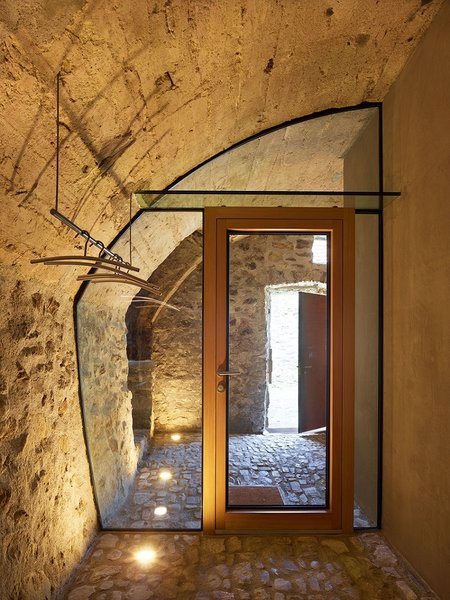 "Dramatic floor lighting on this glass wall, custom fit within the curve of a carved-out stone wall, provides simple beauty in material contrast. ""In such small spaces, it's often better to integrate the furniture and fixtures into the room,"" says de Meuron. Photo 5 of Scaiano Stone House modern home"