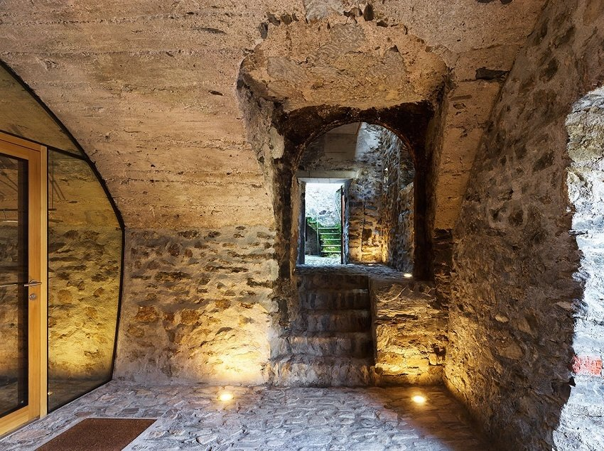 Parts of the interior still maintain an earthy, subterranean atmosphere. Catacombs are hidden below the finished rooms above. The stairs lead to an outdoor area designed for communal interaction.