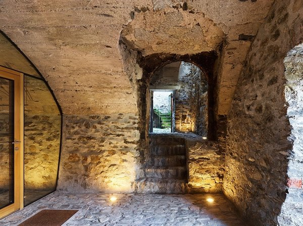 Parts of the interior still maintain an earthy, subterranean atmosphere. Catacombs are hidden below the finished rooms above. The stairs lead to an outdoor area designed for communal interaction. Photo 7 of Scaiano Stone House modern home
