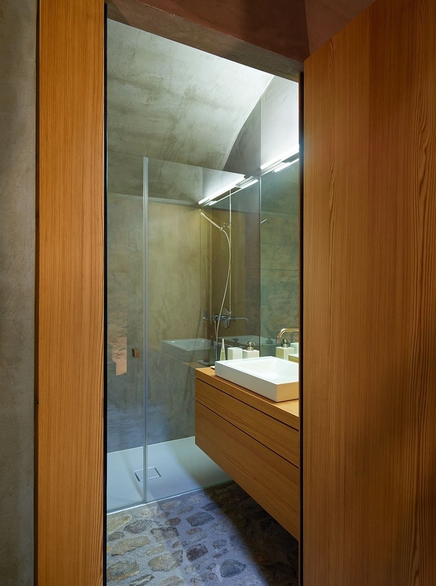 Custom case work and a polished wall give the bathroom a warm yet minimal look.