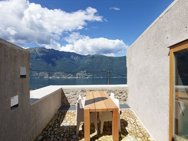 Despite the raw materials and rocky walls, the upstairs terrace feels positively weightless, offering spectacular views of Lago Maggiore. Photo 9 of Scaiano Stone House modern home