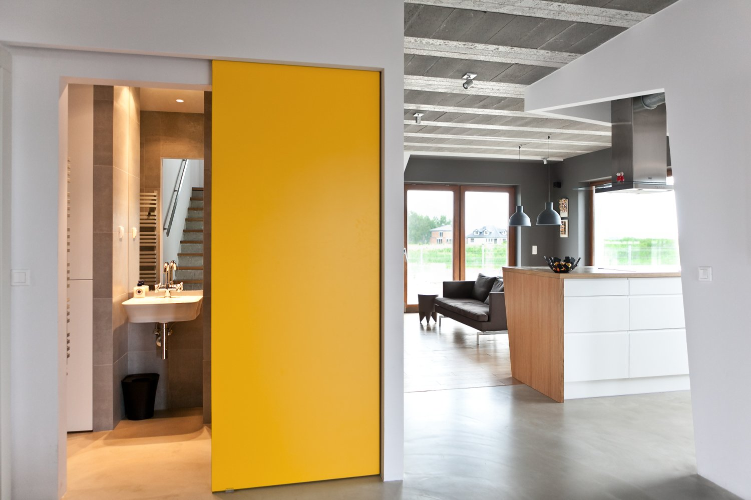 Canary yellow doors keep the house from feeling austere. The sliding function also saves space. Tagged: Kitchen, White Cabinet, and Wood Counter.  Photo 25 of 25 in 25 Bold Ways to Decorate with Yellow from How to Decorate With Yellow (Without the Smiley-Face Connotations)