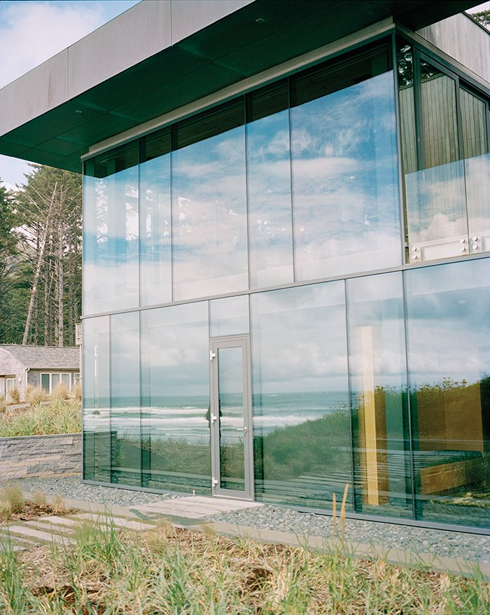 Architects Stan Boles and Christopher Almeida arranged ten-foot-tall panes of glass in a steel curtain-wall frame to create the building's distinctive facade. Tagged: Exterior, Flat RoofLine, House, and Glass Siding Material.  Photo 3 of 9 in Glass House with Stunning Pacific Ocean Views