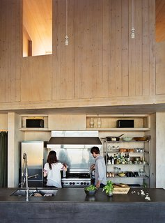 "Learn How to Connect with Nature from This Off-the-Grid Prefab - Photo 2 of 9 - The kitchen island is topped with PaperStone in slate and wrapped in the same steel used to clad the house's facade. ""We matched the color to create a '2001: Space Odyssey' monolith,"" Garlick says. He and his wife, Susan Elliott, a chef, cook at the commercial Wolf range they purchased at a restaurant supply store."