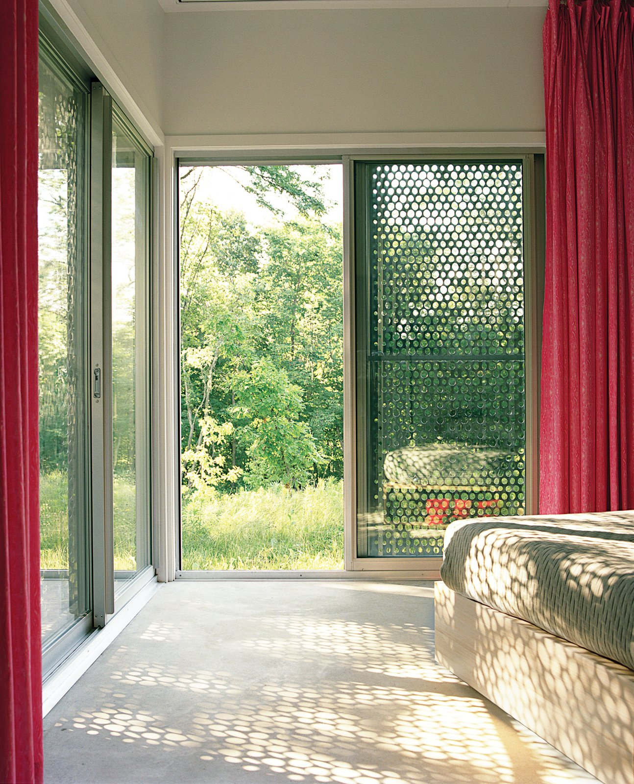 In the master bedroom, the same perforated material that was used in the bathroom gives a sense of sunlight filtering through leaves.  Photo 4 of 12 in 5 Sustainable Ways To Beat the Heat Without Air Conditioning from New Grass Roots