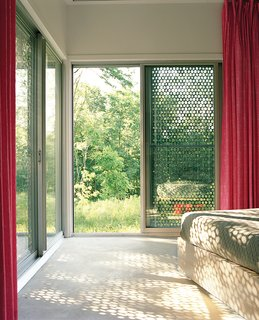 5 Sustainable Ways To Beat the Heat Without Air Conditioning - Photo 3 of 11 - Perforated metal on the exterior of this home filters light coming in, providing shade and a desired aesthetic effect on the interior and exterior.