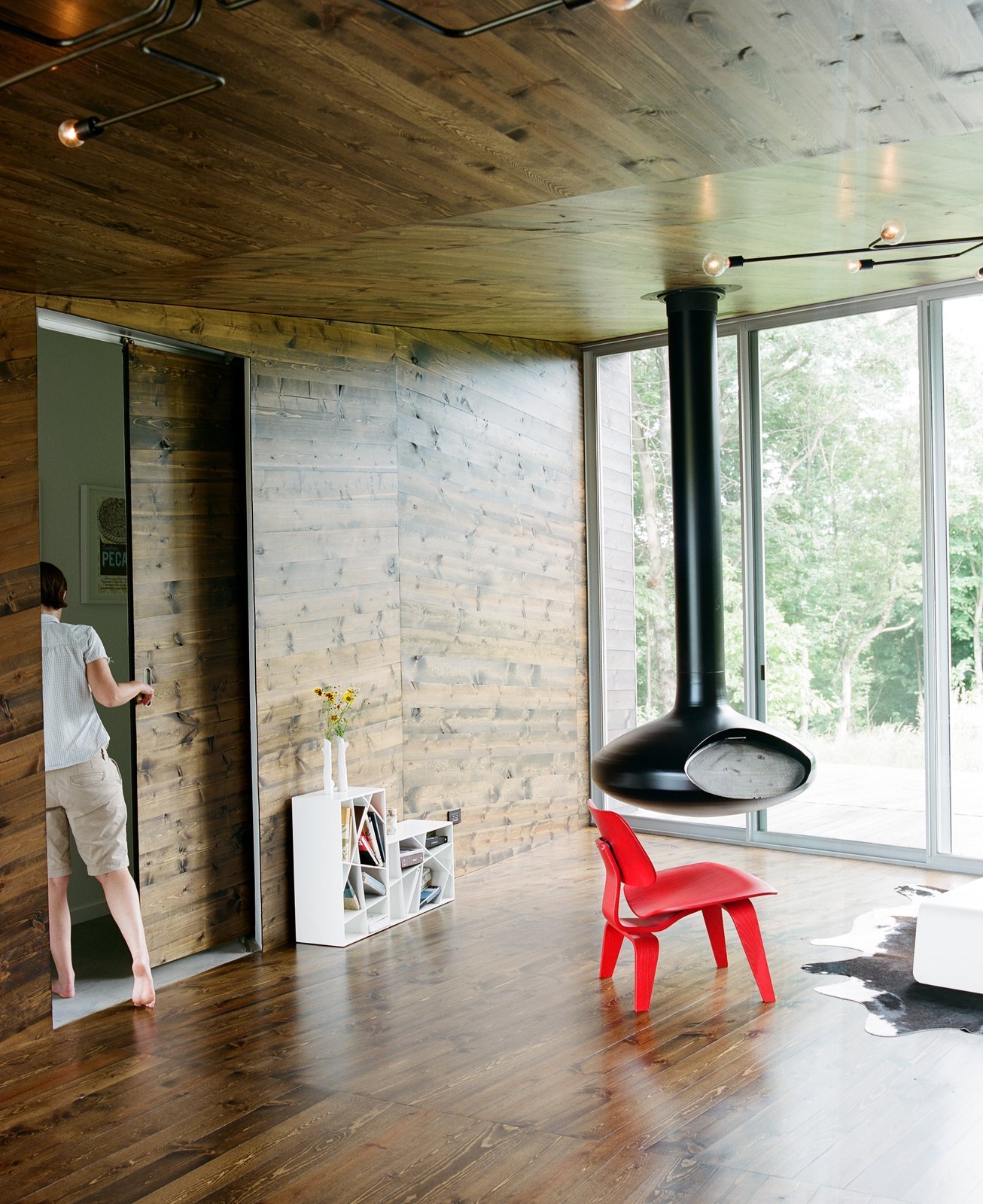 Though minimal, the furnishings in the living room each make a statement. The red molded plywood Eames chair for Herman Miller sits within warming distance of the suspended fire orb. Tagged: Living Room, Hanging Fireplace, Chair, Medium Hardwood Floor, and Rug Floor.  New Grass Roots by Dwell