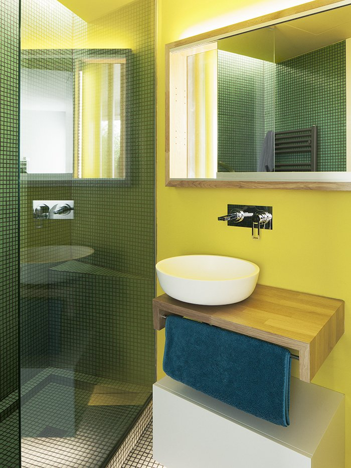 """""""The bathrooms were conceived as special spaces,"""" Vázquez says. """"We decided to give them some color that would contrast with the main spaces."""" A vessel sink by Cubik rests on a custom oak base; the mosaic tile is from Mosaico.  Bathroom Ideas by Tom Berna from Considering the Modern Kitchen and Bathroom"""