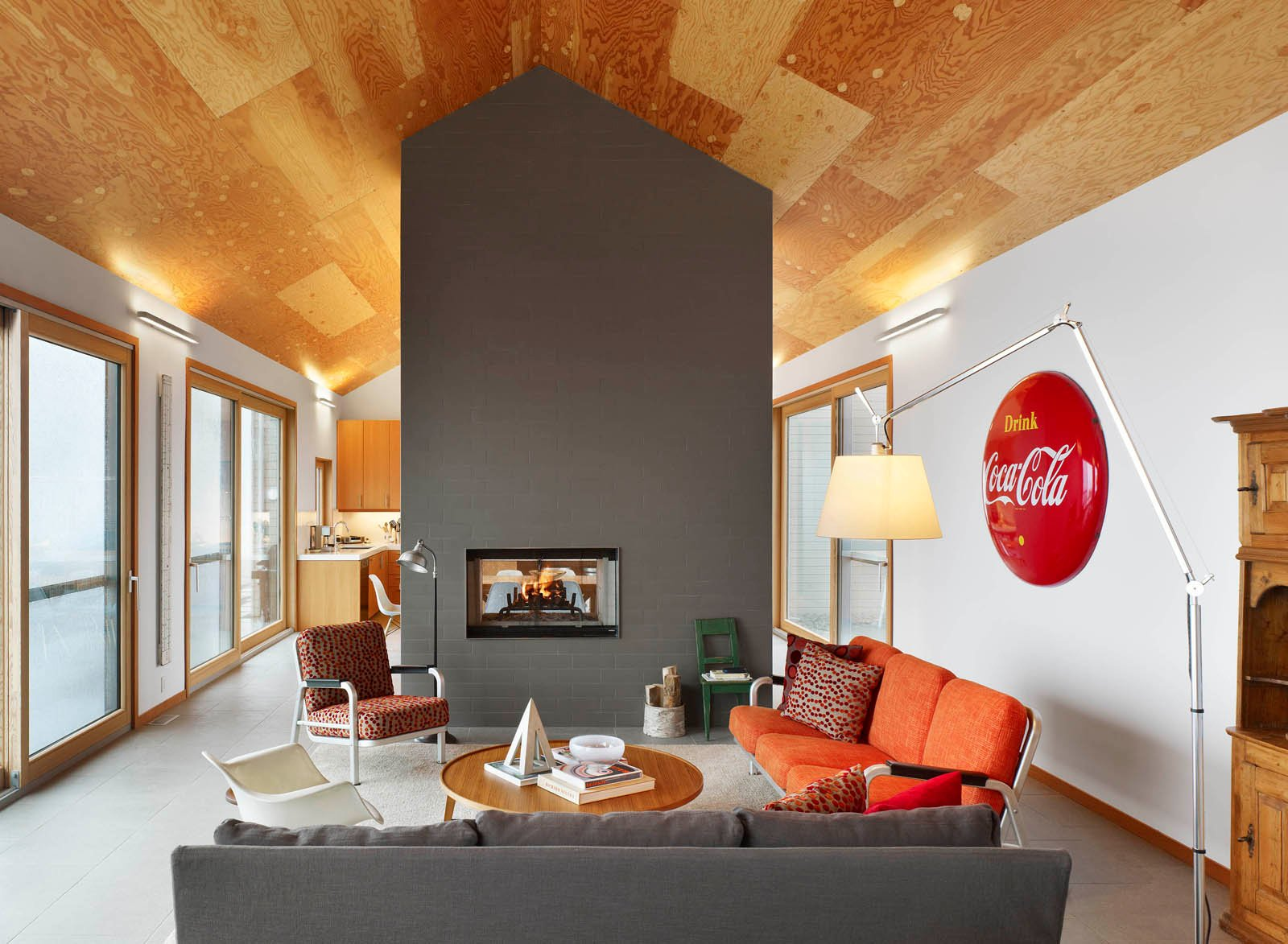 """Having found a 100-acre farm in Ontario featuring rolling corn fields, the residents asked architect Cindy Rendely to design a place that was """"comfortable and modern and appropriate for the country."""" Though technically all one space, the living room, dining room, and kitchen are separated by the double-sided fireplace."""