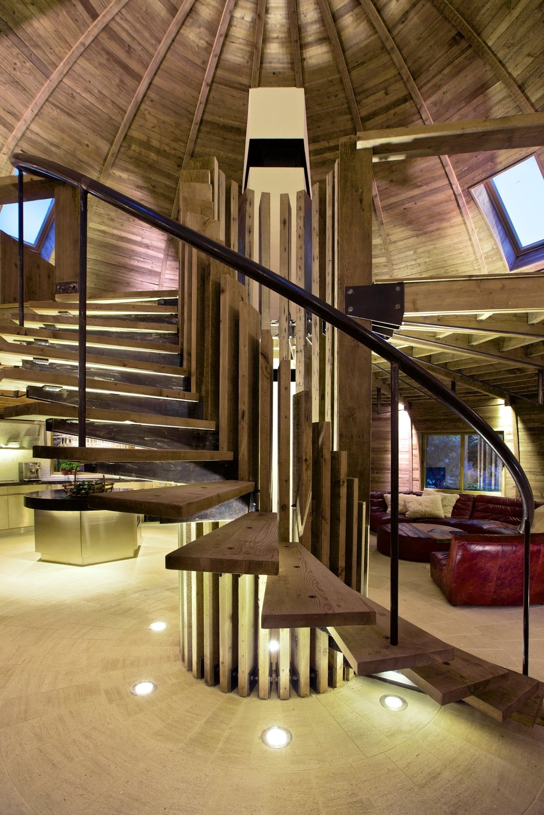 A sweeping spiral staircase occupies the center of the self-supporting dome. Its reclaimed pine treads echo the dome's ceiling and contrast pleasantly with the raw steel railing. PAK LED lights installed in the floor add an extra touch of drama to the home's showpiece.