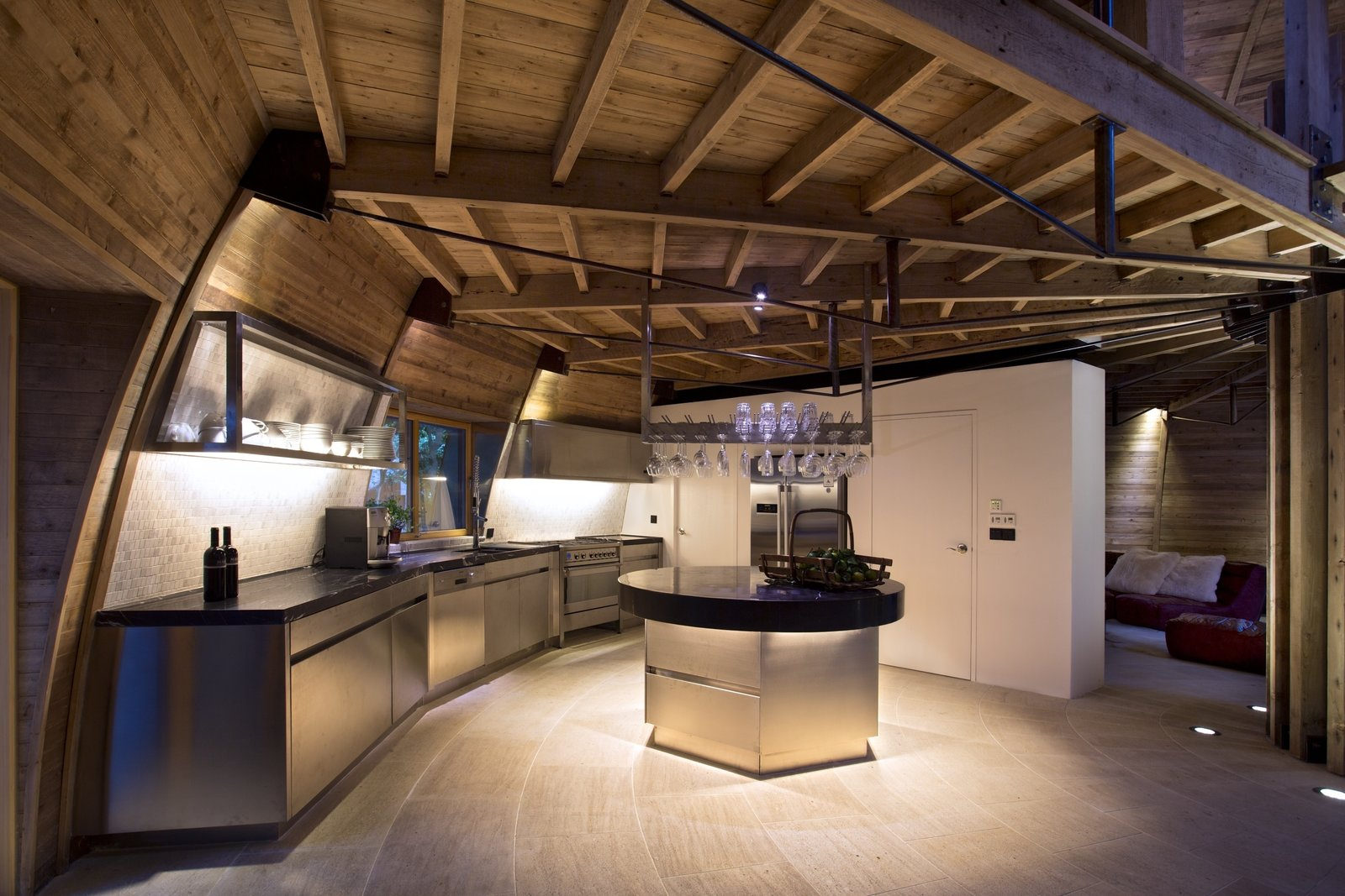 A full-service kitchen is nestled under the dome's loft. Clad in stainless steel, its custom-made cabinets match the appliances and the wine glass holder that hangs over the island. The kitchen's black marble countertops echo the surface of the dining table.