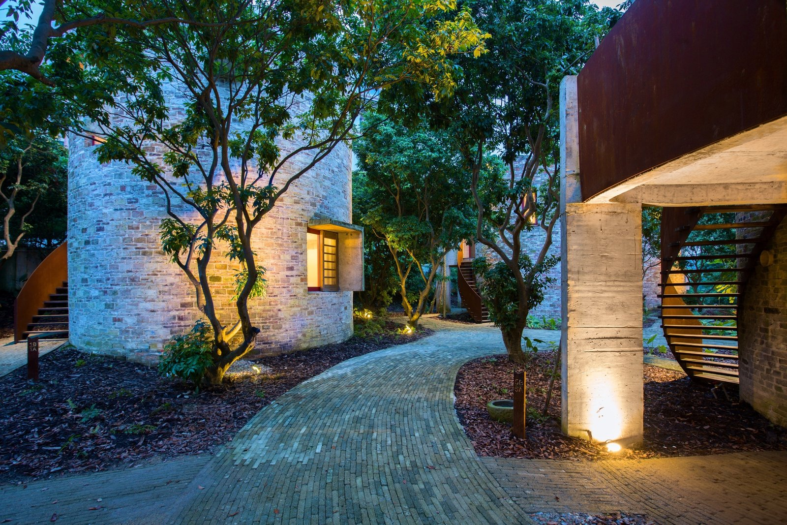 The Dome Home is part of a small community that also features seven round houses designed to accommodate designers and visitors. These round towers are all clad in reclaimed bricks. The Dome Home's visual cues continue throughout the village, manifesting themselves in the form of curving paths and staircases.