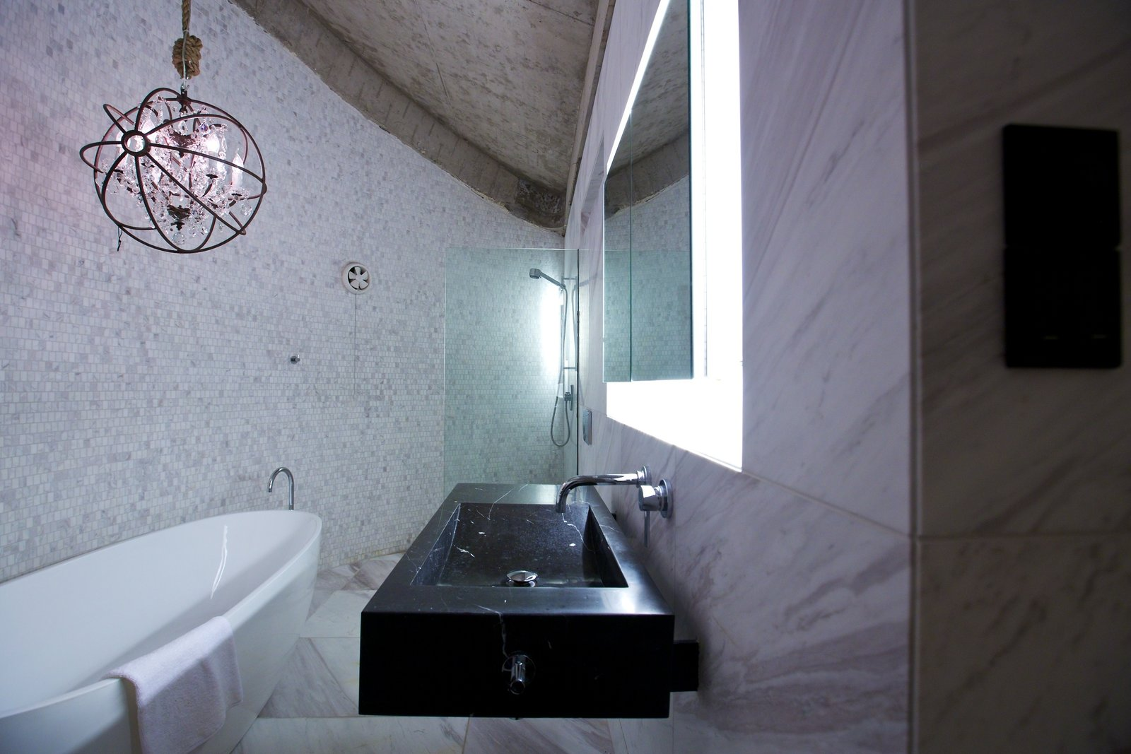 In the Round House's bathroom, a custom black marble basin protrudes from the white marble-tiled walls. Smaller tiles follow the curve of the house's outer wall, a curve that is echoed by the sculptural white bathtub, which sits under a Timothy Oulton Gyor crystal chandelier.  Photo 8 of 8 in A British Furniture Brand Built This Round Village in China