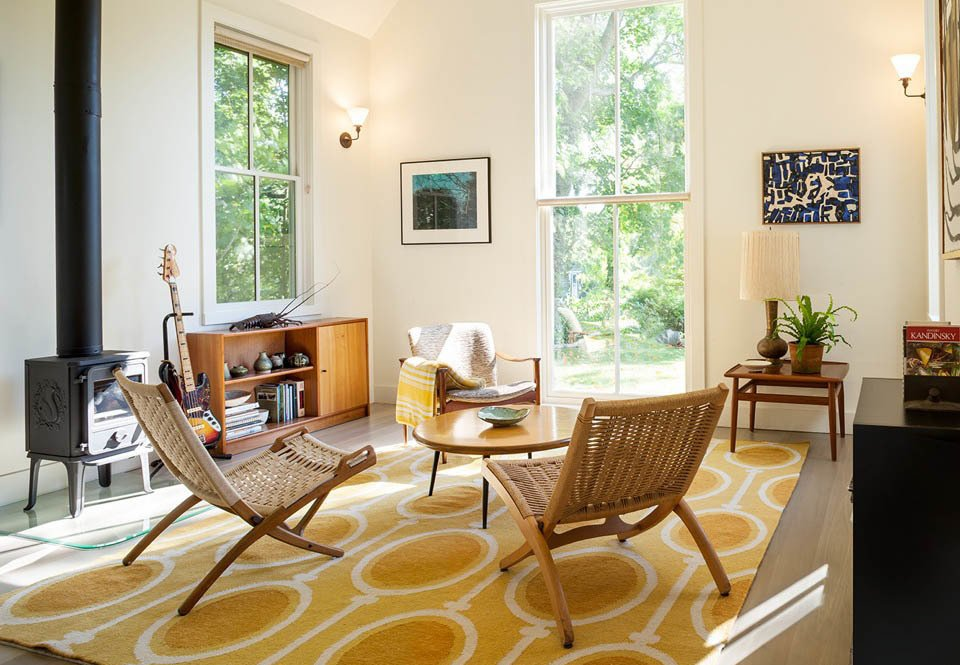 Jane and Dan Wright furnished the living space of their new studio building with a rug from West Elm and a wood stove from Morsø.  Photo 1 of 7 in A Modern Live-Work Studio in Rhode Island