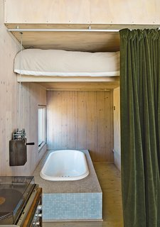 Learn How to Connect with Nature from This Off-the-Grid Prefab - Photo 5 of 9 - Taking inspiration from train cabins, the guest bed lifts to reveal a bathtub. Garlick made the mechanism using sailboat hardware. The velvet curtain is by Restoration Hardware and the tile is from Stone Tile.