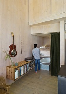 Learn How to Connect with Nature from This Off-the-Grid Prefab - Photo 6 of 9 - The floating bookshelf is composed from wood found on the property. Garlick purchased the Technics turntable and receiver from a used audio store.