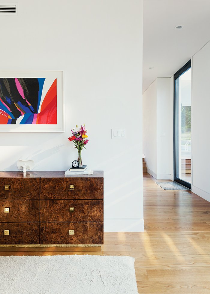 The 1970s burlwood dresser is originally from a Palm Beach estate. Modernist sculptures throughout the house are by artist Costantino Nivola; abstract artwork is by Charles Schorre. Cute Couple Alert: Modern Prefab Poolhouse Addition to a 1920s Sears Kit House - Photo 2 of 11