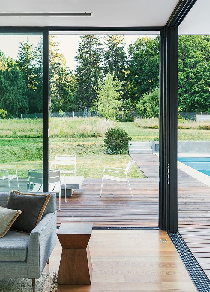 The aluminum sliding glass door system, manufactured by Solar Innovations, comprises five seamless panels that meet at the corner. Tagged: Living Room, End Tables, Sofa, and Light Hardwood Floor.  Photo 7 of 11 in Cute Couple Alert: Modern Prefab Poolhouse Addition to a 1920s Sears Kit House