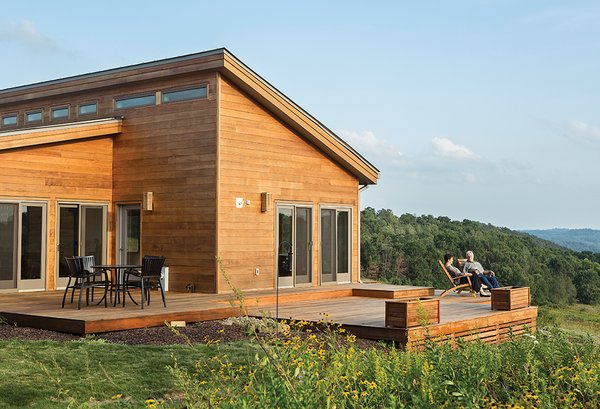 Karen Ellzey and Tim Wright gaze at the hills of Wisconsin's Driftless Area from the deck outside their prefab house by Blu Homes. The Brant Natural Folding Chairs are from Crate and Barrel, and the Strata chairs and wrought-aluminum patio table are by Summer Classics.