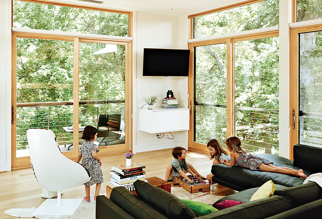The living area is furnished with a Fjord swivel arm chair by Patricia Urquiola for Moroso and a Como sectional chaise by Giorgio Soressi. Tagged: Living Room, Sofa, Chair, and Light Hardwood Floor.  Photo 4 of 11 in Modular Compound is the Ultimate Retreat for Three Generations