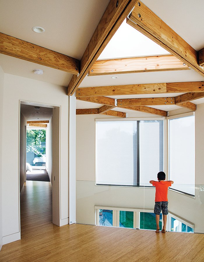 The couple's son, Rio, pauses on the mezzanine, which leads to the bedrooms. Tagged: Hallway and Light Hardwood Floor.  Photo 4 of 12 in 28 Triangles Make Up This Hyper-Angular Family Home
