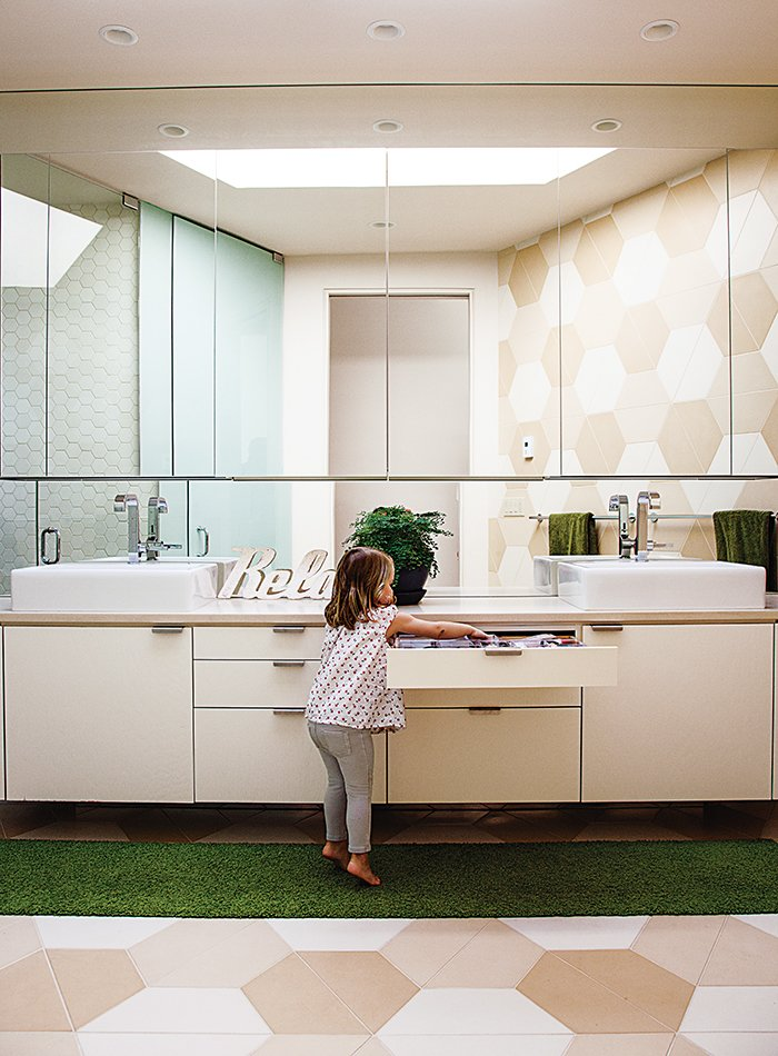 Hexagonal tiles made by the Portland Cement Company continue the pattern in the bathroom, where the architect designed low drawers and cabinets that are easy for Luna to reach. Tagged: Bath Room.  Photo 8 of 12 in 28 Triangles Make Up This Hyper-Angular Family Home