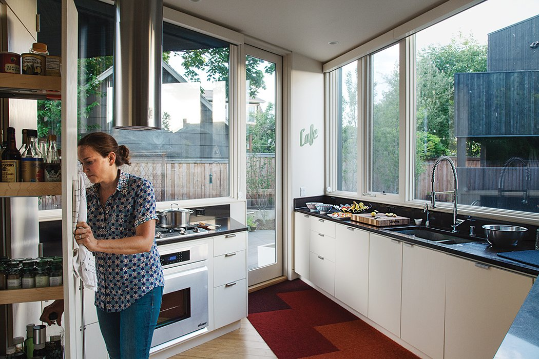 """My favorite spot is the kitchen,"" says Kaja Taft of the prefab home she shares with her family in Portland. ""I can stand in it and cook and converse with everyone."" The space overlooks the back yard. The white-oak cabinetry is by HOMB and the countertops are Caesarstone. A hood by Faber is above a Dacor range. Tagged: Kitchen, White Cabinet, Light Hardwood Floor, Granite Counter, and Range.  Photo 10 of 12 in 28 Triangles Make Up This Hyper-Angular Family Home"