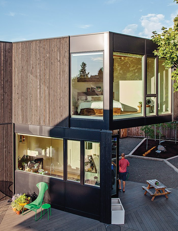 The master bedroom is perched above the kitchen. Kovel designed the landscaping with Kitty Davis of LandCurrent and Glenn Nardelli of Pistils Landscape Design + Build. Tagged: Exterior, Wood Siding Material, House, Flat RoofLine, and Metal Siding Material.  Photo 11 of 12 in 28 Triangles Make Up This Hyper-Angular Family Home