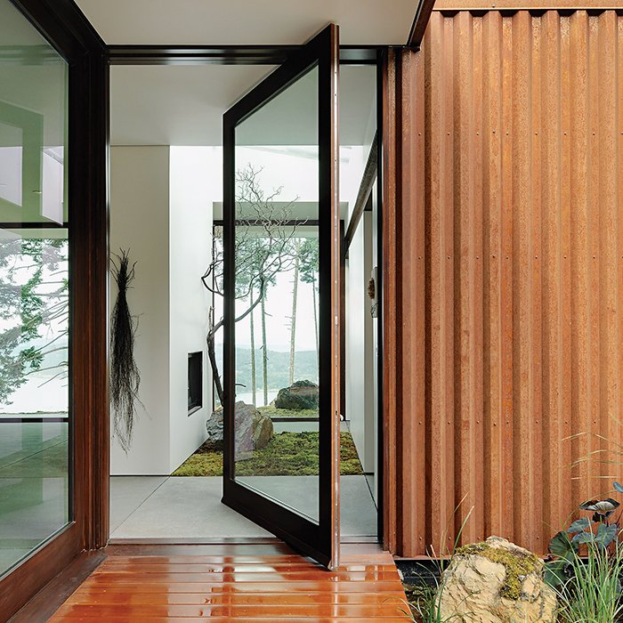 The Orcas Island house, whose steel exterior has patinaed to a rusty hue has a wide doorway with a pivoting door and a zero-step threshold.  Photo 2 of 8 in Architects Dream Up Truly Inviting Housing Options for Aging Population