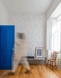 The blue entry door packs a punch in the neutral living area, which is sparsely furnished with inexpensive pieces — some from local Portuguese companies, others self-made or purchased in flea markets.