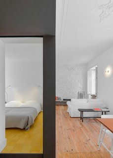 7 Minimalist Apartments Around The World - Photo 6 of 7 - José Andrade Rocha brought a 592-square-foot apartment in Lisbon back to life by restoring its original, early 20th-century materials, strengthening its relationship with the street, and defining its public and private spaces. A series of gray sliding doors divide the living spaces.
