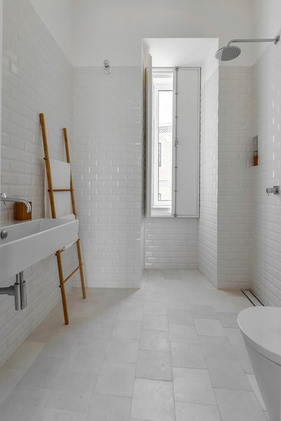 """White tiles — hydraulic ones on the floor and """"biselado"""" (meaning """"beveled"""") ones on the walls — make for a tranquil bathroom."""