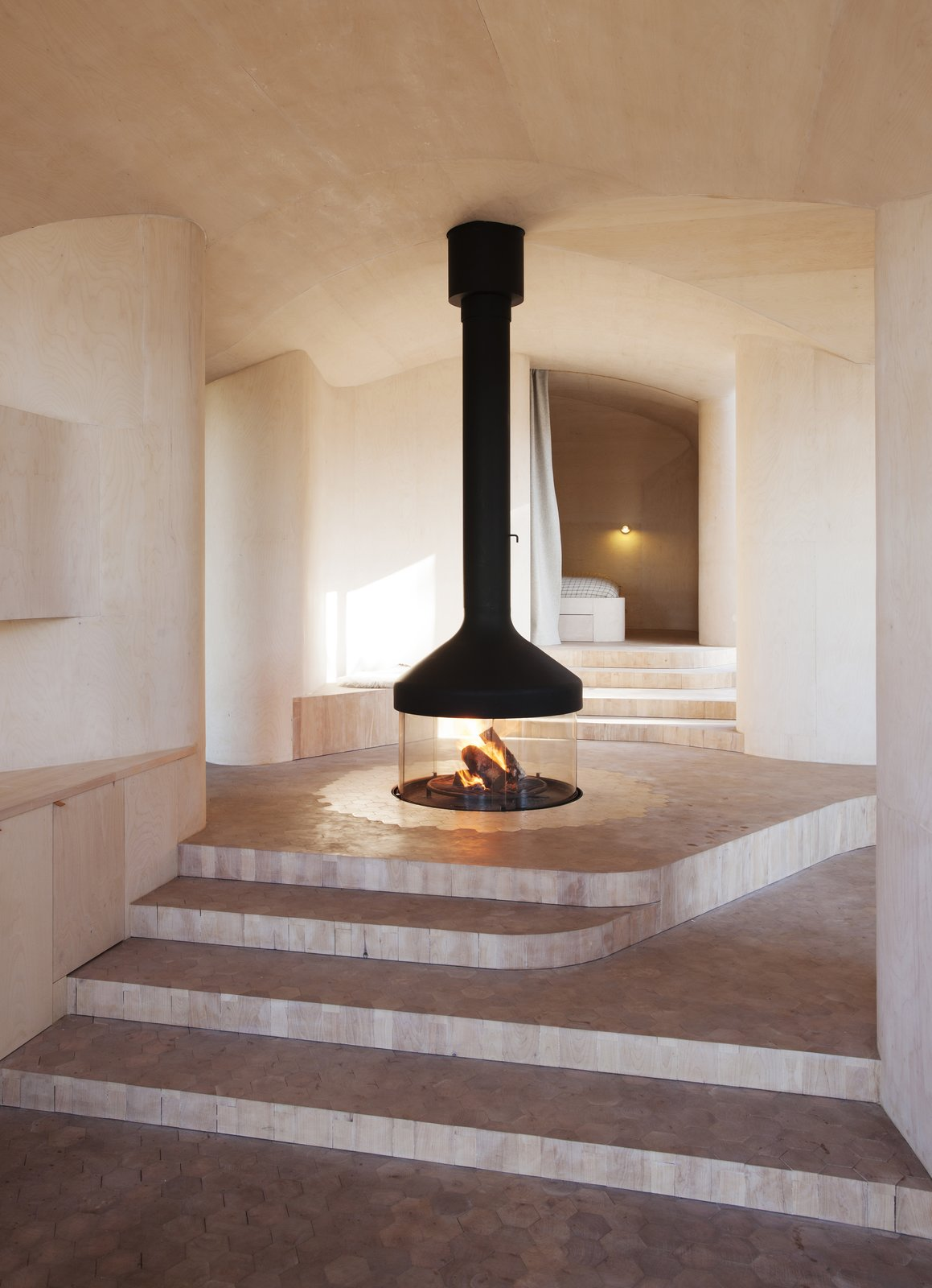"The layout revolves around a central ""campfire"" that burns beneath a suspended mantel. Since it's located at the access level, the fireplace's flickering warmth can be enjoyed throughout the house. The surrounding floor is covered with hexagon tiles cut from marble, which transition into tiles made of birch log in the rest of the house. Tagged: Living Room, Hanging Fireplace, and Marble Floor.  Modern Winter Retreats by Aileen Kwun from Cabin Norderhov"