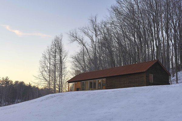 Durability was an important factor in the building's exterior. The architect selected materials, such as weathering steel for the roof and charred cedar for the siding, which would age gracefully. The deep browns and reds also blend into the forested landscape. Photo  of Off-Grid Retreat modern home