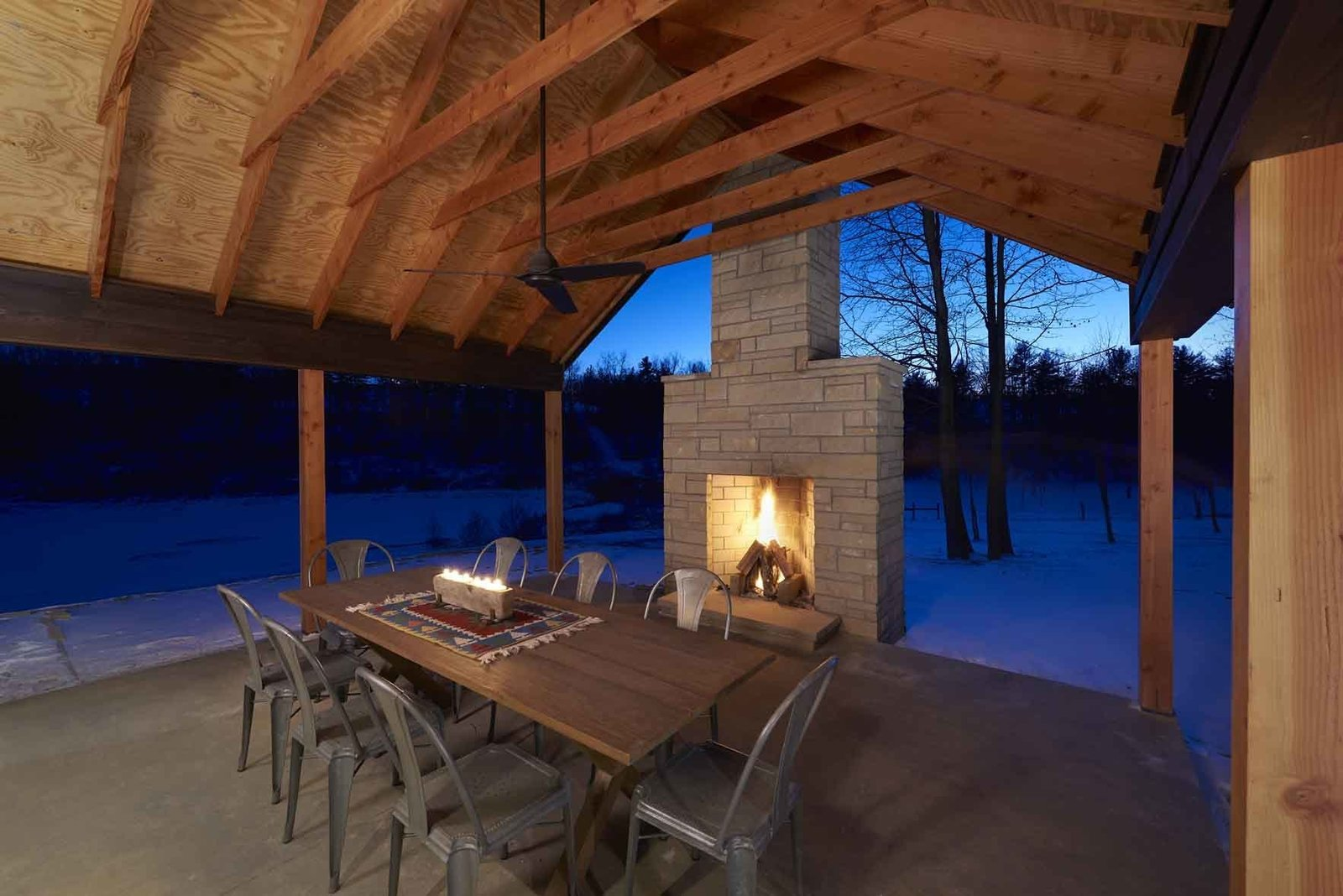Douglas fir columns frame views from the porch, located just adjacent to the living, dining, and kitchen space. A sandstone fireplace bookends this space, creating a sheltering and warming effect.  Off-Grid Retreat by Zachary Edelson